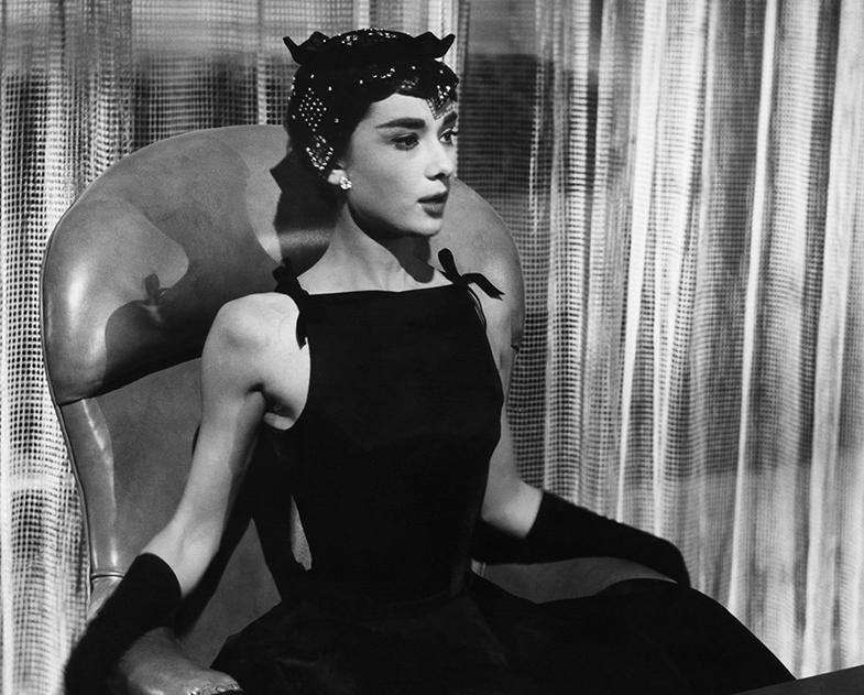Audrey con el vestido negro de escote alto que cubría sus clavículas y que desde ese momento pasó a conocerse como 'escote Sabrina'. © Cordon Press