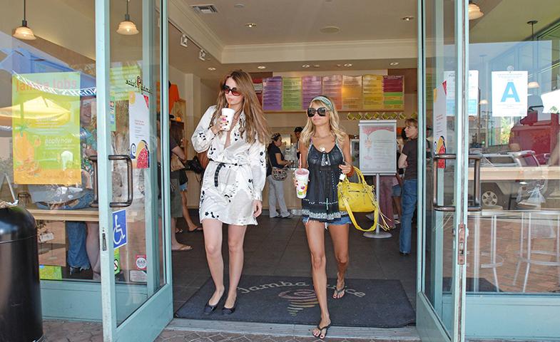 Mischa Barton y Nicole Richie (con el 'City' colgando del brazo) en una instantánea que podría resumir a la perfección el estilo de los primeros dos miles: estilo boho -dictado por Rachel Zoe- maxi gafas, zapato plano, bolso de marca... y vaso de café en la mano.