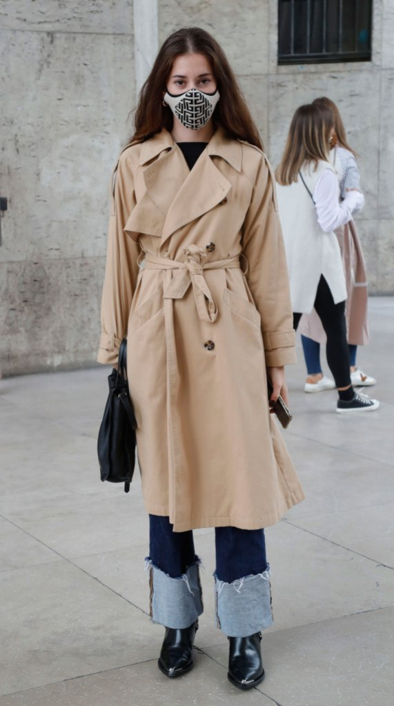 Paris Fashion Week Street Style: Woman wears a trench coat, mask, jeans, and black boots.
