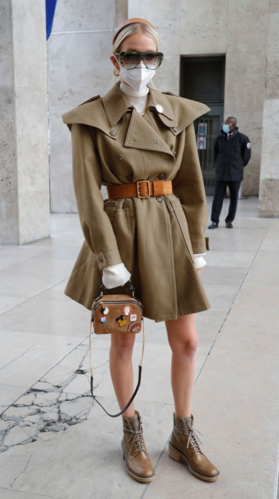 Paris Fashion Week Street Style: Woman wears a trench dress, mask, and combat boots.
