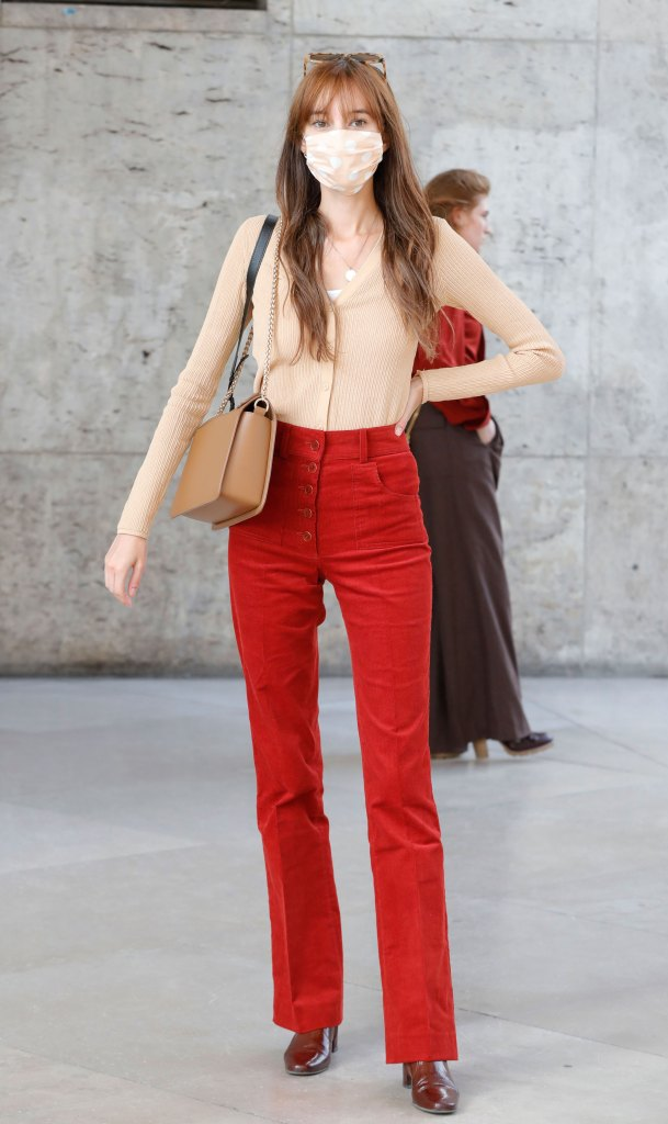 Paris Fashion Week Street Style: Woman wears a beige top, mask, and red high-waisted pants.