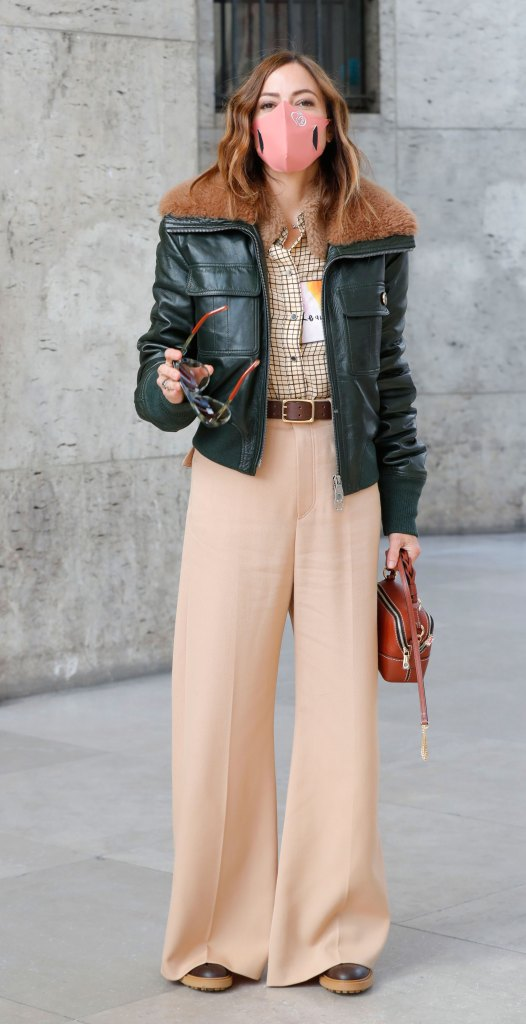 Paris Fashion Week Street Style: Woman in a leather coat, a pink face mask, and beige pants.